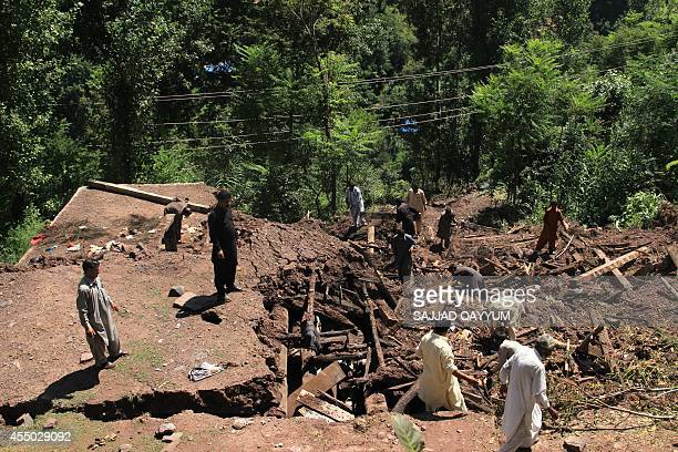 Pakistani Kashmiri people salvage belongings from the debris of their destroyed mud houses after landslides caused by heavy monsoon rain at Puna...