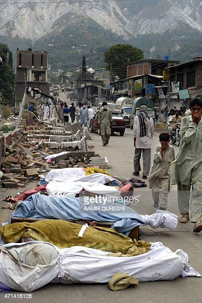 Pakistani Kashmiri people walk past the bodies of earthquake victims in a street in the earthquake hit area in Muzaffarabad the capital of the...
