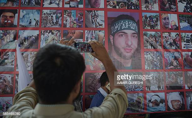 Pakistani Kashmiri protester takes a photograph of a poster bearing the image of Hizbul Mujahideen commander Burhan Wani as other protesters block a...