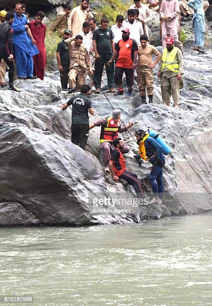 Pakistani Kashmiri rescuers search for the bodies of the victims of a passenger bus plunged into a fastflowing Neelum river at 50 kilometers north of...