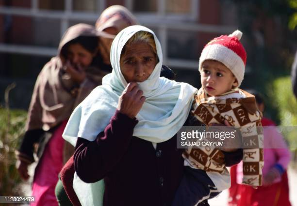 Pakistani Kashmiri residents who were evacuated from the border town of Chakothi walk in a school used as a temporary shelter in Hattian Bala town in...