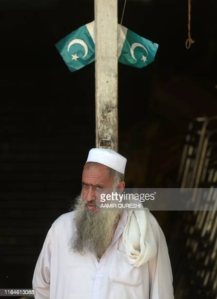A Pakistani Kashmiri vendor looks on outside his shop at a market near the Line of Control the de facto border between Pakistan and India in Chakothi...