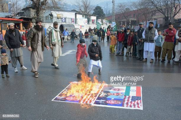 Pakistani Kashmiris burn portraits of US President Donald Trump and Indian Prime Minister Narendra Modi along with the US and Indian national flags...