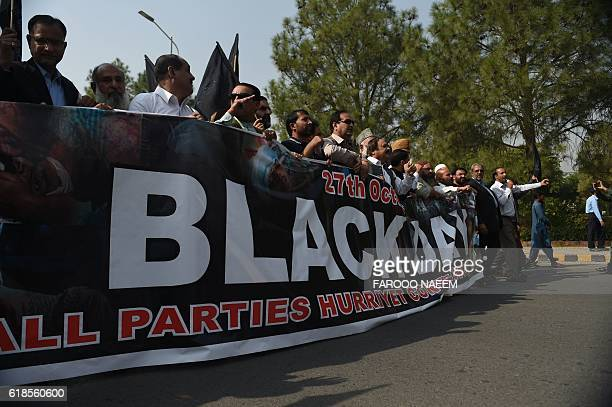 Pakistani Kashmiris shout slogans as they walk behing banners during a protest in Islamabad on October 27 as they observe 'Black Day' Pakistani...