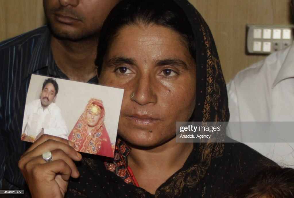Pakistani Khalida Parveen, sister of Farzana Parveen, punished with stone to death by her father and other family members for marrying a man of her own choice, shows the picture of her sister during a press conference in Lahore, Pakistan on May 31, 2014. A Pakistani court extended the detention period of the father, for extra time to investigate the crime, police said. Farzana Parveen died after the attack, with stones and bricks, of more than two dozen people including relatives, outside Lahore's High Court on May 27 for marrying against her family's wishes.