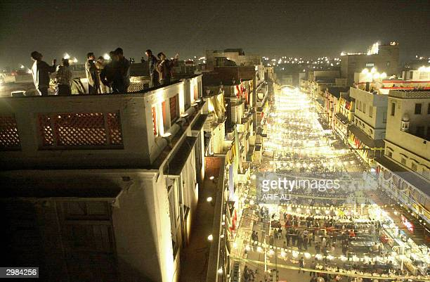 Pakistani kite enthusiasts fly their kites on a roof as below them a street shines with lighting decorations to mark the first night of the Spring...