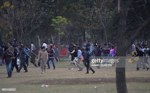 Pakistani kite flyers run from police at a park in Islamabad on March 12 during the Basant Kite Festival which is traditionally celebrated in spring...
