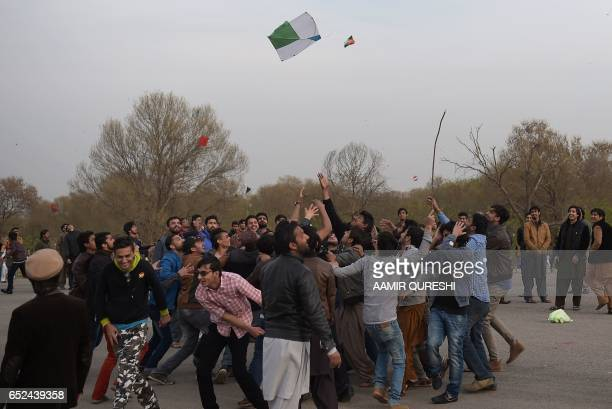 Pakistani kite flyers try to catch a kite at a park in Islamabad on March 12 during the Basant Kite Festival which is traditionally celebrated in...
