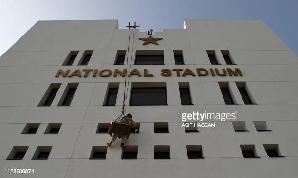 A Pakistani labourer paints a facade of the National Cricket Stadium building in Karachi on March 4 2019 Pakistan Super League popularity has surged...