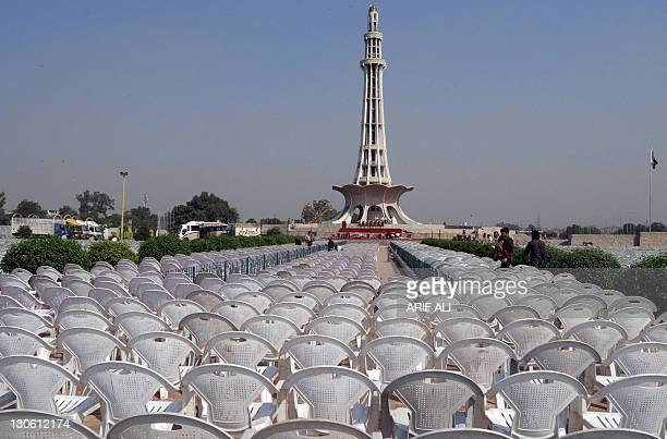 Pakistani labourers arrange chairs in front of the MinarePakistan minaret at Iqbal Park in Lahore on October 27 2011 ahead of a public meeting by...