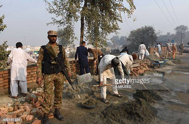Pakistani labourers build the wall of an army run school which was attacked by Taliban militants in Peshawar on December 21 2014 Hundreds of...