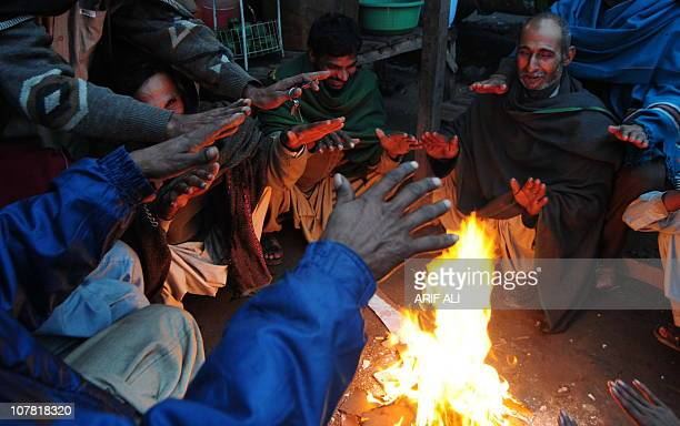 Pakistani labourers warm themselves around a fire during the seasonal wintry rainfall in Lahore on December 30, 2010. The Pakistan Meteorological...