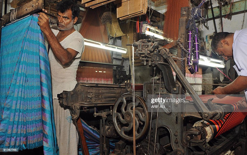 Pakistani labourers work at a textile factory in Lahore on September