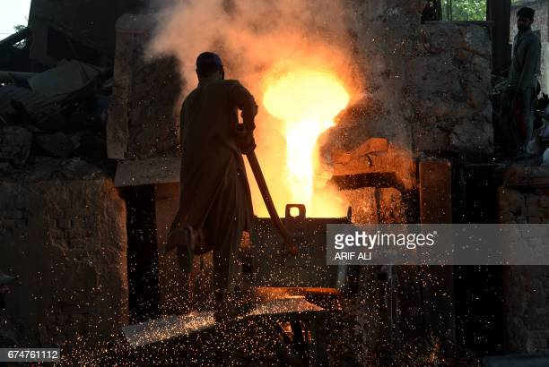 TOPSHOT Pakistani labourers work at an iron factory on the eve of International Workers' Day in Lahore on April 29 2017 / AFP PHOTO / ARIF ALI