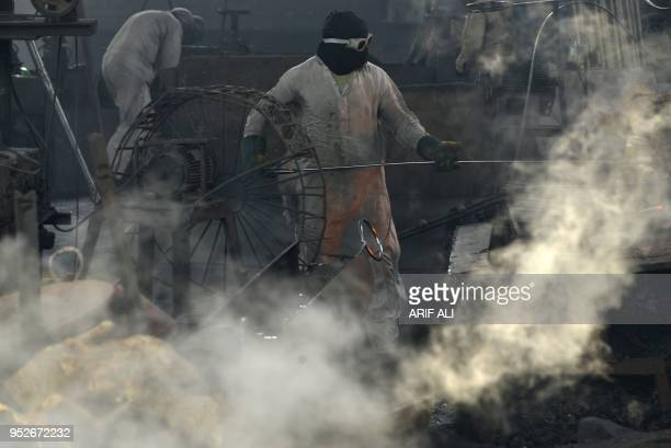 Pakistani labourers work in an iron factory in Lahore on April 28 ahead of International Workers' Day