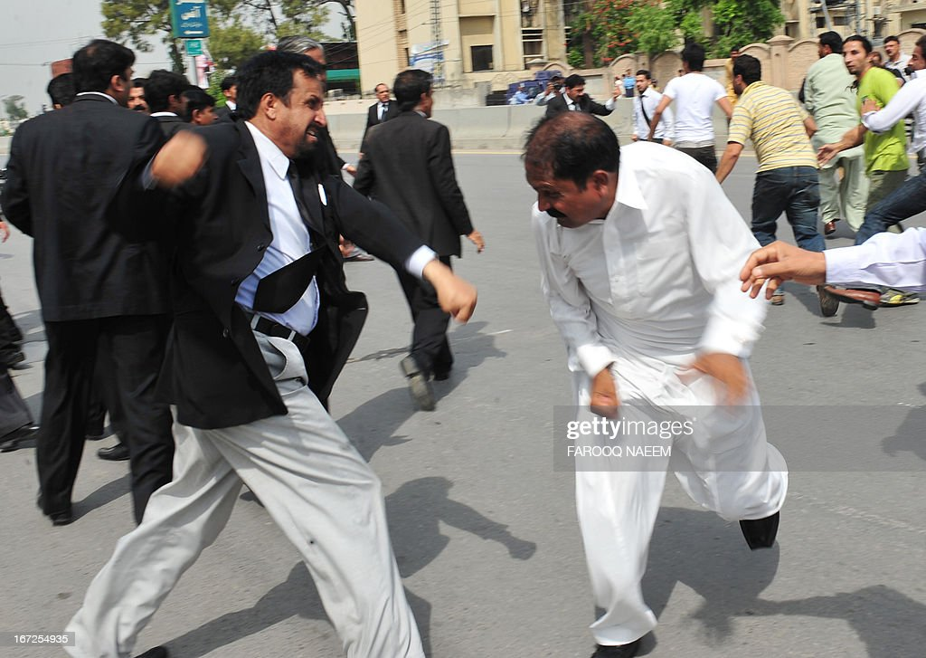 A Pakistani lawyer (L) and a supporter of former military ruler Pervez Musharraf engage in fisticuffs outside a court during Musharraf's case hearing in Rawalpindi on April 23, 2013. Musharraf appeared before an anti-terrorism court for the first time over the murder of former prime minister Benazir Bhutto. AFP PHOTO/Farooq NAEEM