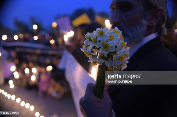 A Pakistani lawyer holds flowers as he takes part with civil society activists holding lighted candles during a vigil in Islamabad on December 22...