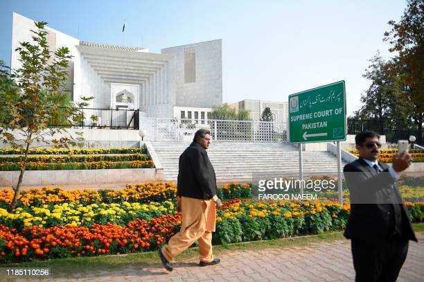 A Pakistani lawyer uses his mobile phone in front of the Supreme Court building during a case hearing suspending the notification of the tenure...