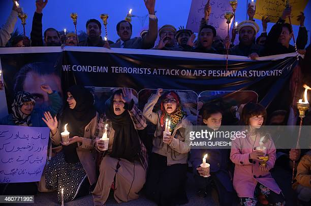 Pakistani lawyers and civil society activists shout slogans as they hold lighted candles during a vigil in Islamabad on December 22 held for...