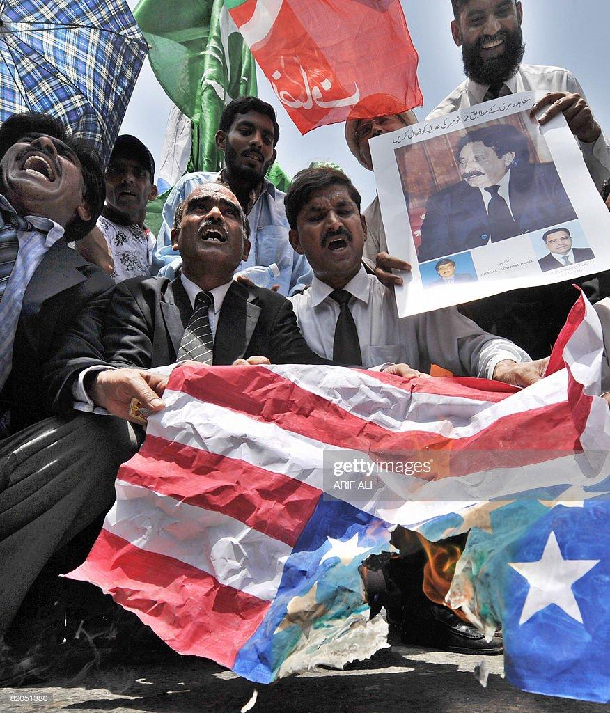 Pakistani lawyers hold a burning US flag : News Photo