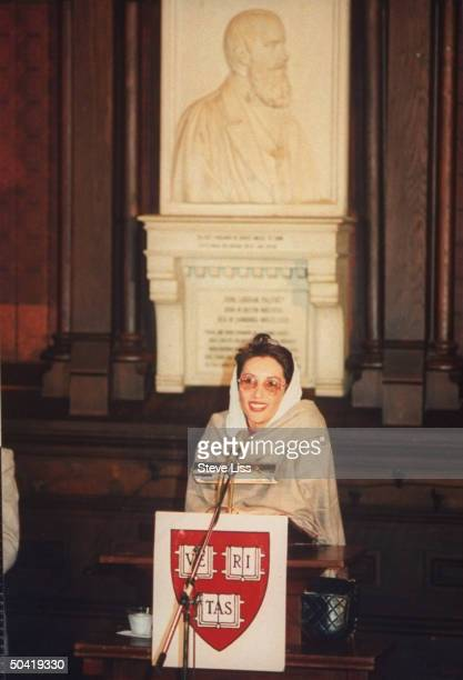 Pakistani ldr Benazir Bhutto speaking at podium w Harvard 'Veritas' coat of arms on it while receiving an honorary degree