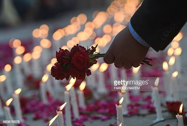 A Pakistani legislator places flowers at a memorial for the children and teachers killed by Taliban militants in army run school at the parliament in...