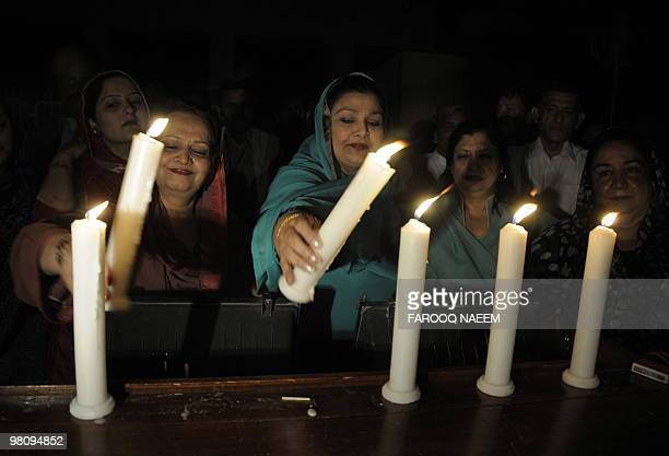 Pakistani legislators and environment ministry employees light candles in front of the National Sssembly as part of Earth Hour in Islamabad on March...