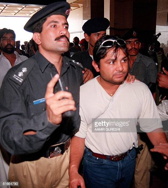 Pakistani legspinner Mushtaq Ahmed is escorted out of the airport lounge by security guards here 24 June 1999 as nine members of Pakistan's world cup...