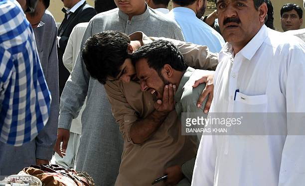 Pakistani local journalists react over the body of a news cameraman after a bomb explosion at a government hospital premises in Quetta on August 8...