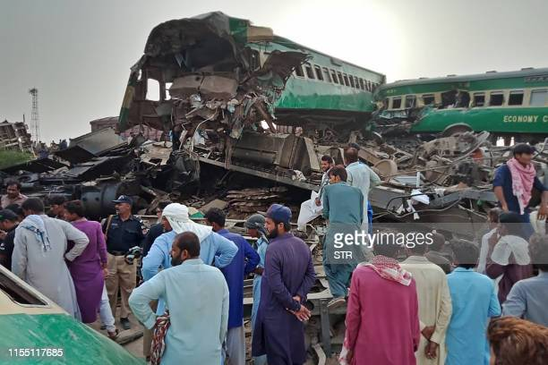 Pakistani local residents gather around the wreckage of carriages at the site where two trains collided in Rahim Yar Khan district of Punjab province...