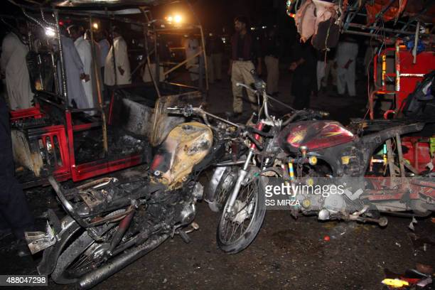 Pakistani local residents gather near the wreckage of vehicles after a bomb explosion in Multan on September 13 2015 At least nine people were killed...