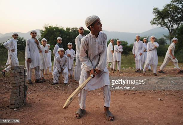 Pakistani madrasa students play cricket following the afternoon prayer on November 24 2013 in Islamabad Pakistan Tens of thousands students in the...