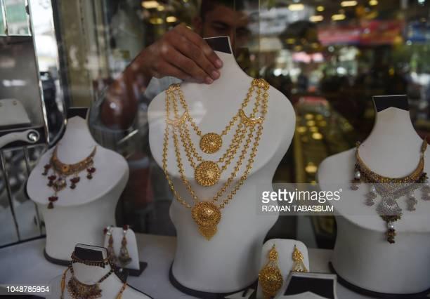 A Pakistani man adjusts jewellery on display at his gold shop in Karachi on October 10 2018 The International Monetary Fund said October 9 Pakistan...