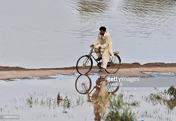 A Pakistani man bicycles down a narrow path of dry earth in Camp Kuroona village in Nowshera on August 9 2010 Around 138 million people have been...