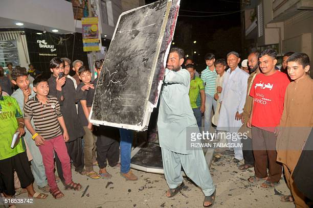 A Pakistani man breaks a TV set after his team lost a cricket match against India during the World T20 cricket tournament on March 19 2016 in Karachi...