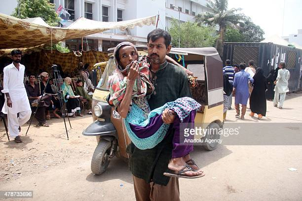 Pakistani man carries a heatstroke victim to a hospital in Karachi Pakistan on June 27 2015 After a week of extreme conditions the effects of a...