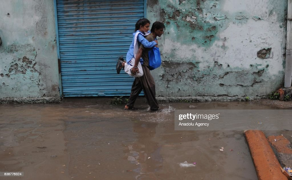 Pakistani man carries his daughter on his back as he wades through a flooded street after heavy monsoon rains hit the city of Rawalpindi Pakistan on..