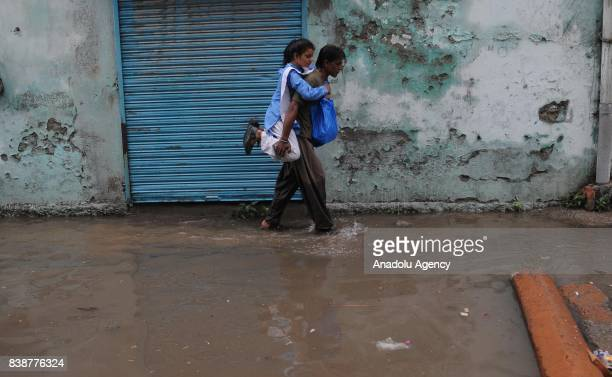 Pakistani man carries his daughter on his back as he wades through a flooded street after heavy monsoon rains hit the city of Rawalpindi Pakistan on...