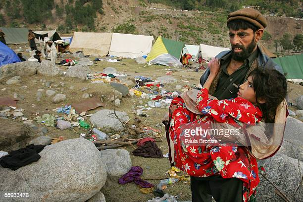 Pakistani man carries his injured daughter back to their tent October 16, 2005 in Balakot, Pakistan. It is estimated that 90% of the city of Balakot...