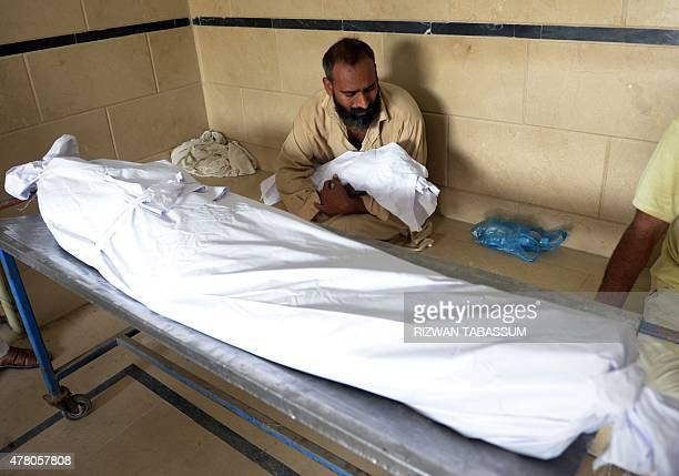 A Pakistani man carries the body of his three yearold son outside the cold storage of the Edhi morgue in Karachi on June 22 after his death during a...