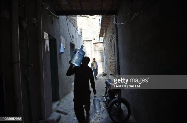 Pakistani man carries water bottles as he walks at a Christian colony in Islamabad on October 31 after the Supreme Court decision to overturn the...