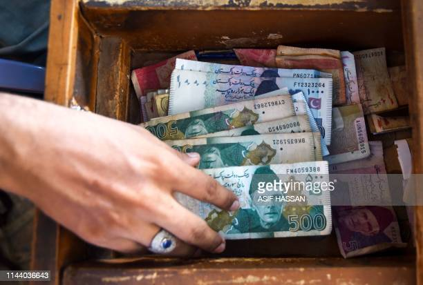 A Pakistani man counts Pakistan's rupees at his shop in Karachi on May 16 2019 Pakistan's rupee dropped to an alltime low of 1465 to the dollar on...