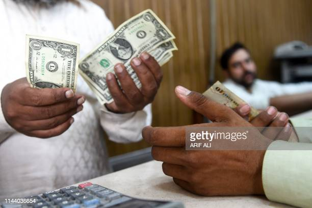 Pakistani man counts US dollars at the currency exchange place in Lahore on May 16, 2019. - Pakistan's rupee dropped to an all-time low of 146.5 to...