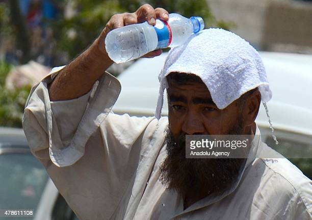 Pakistani man covers his head with a wet towel to avoid heatstroke in Karachi Pakistan on June 26 2015 More than 1000 people have been killed over...