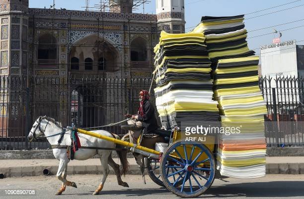Pakistani man drives a horsedrawn carriage loaded with foam sheets on a street in Lahore on January 29 2019
