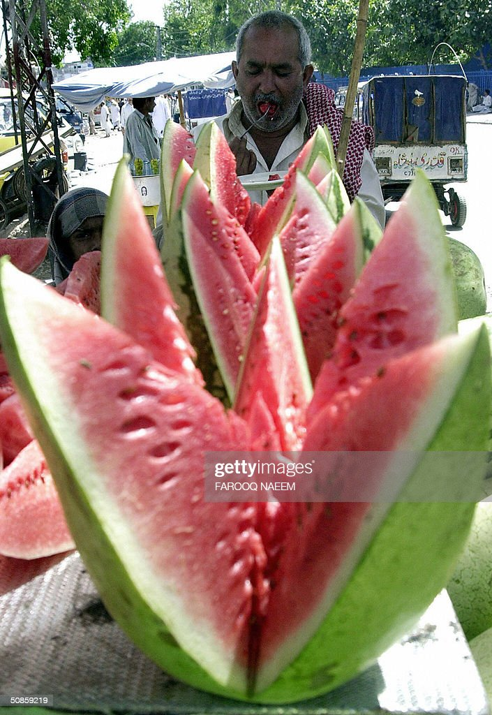 A Pakistani man eats a piece of watermelon at the roadside shop in Rawalpindi, 20 May 2004 during a hot day. Water melon is a popular fruit during summer in this South Asian country. AFP PHOTO/Farooq NAEEM