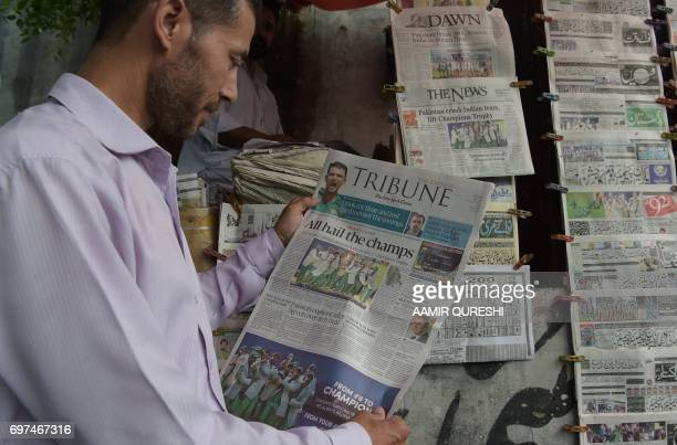 A Pakistani man holds a morning newspaper with front page coverage of Pakistan's victory against India in the ICC Champions Trophy final cricket...