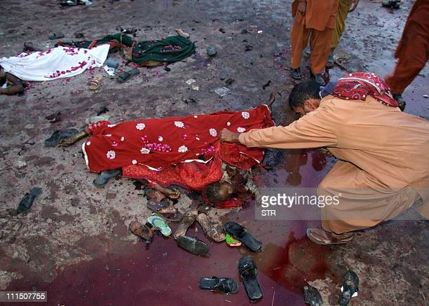 Pakistani man looks at the body of a child next to his mother body following a suicide bomb attacks outside the shrine of 13th century Sufi saint...