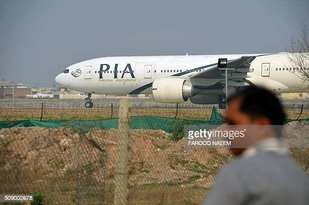 A Pakistani man looks on as a Pakistan International Airline plane taxis on the runway on the way to Saudi Arabia during the PIA employees strike in...
