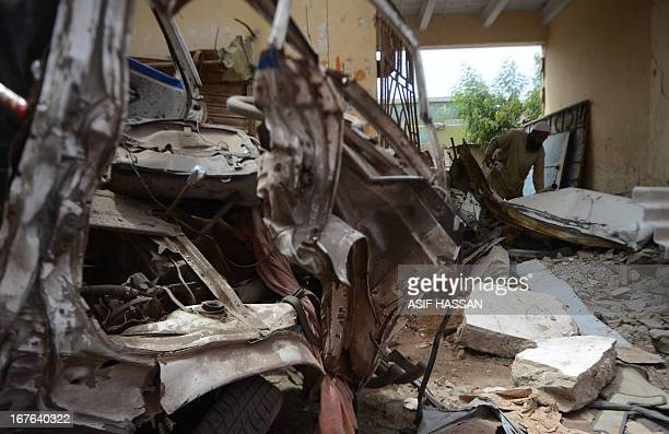 A Pakistani man looks through a damaged building at the site of bomb blast near the Pashtundominated Awami National Party office in Karachi on April...